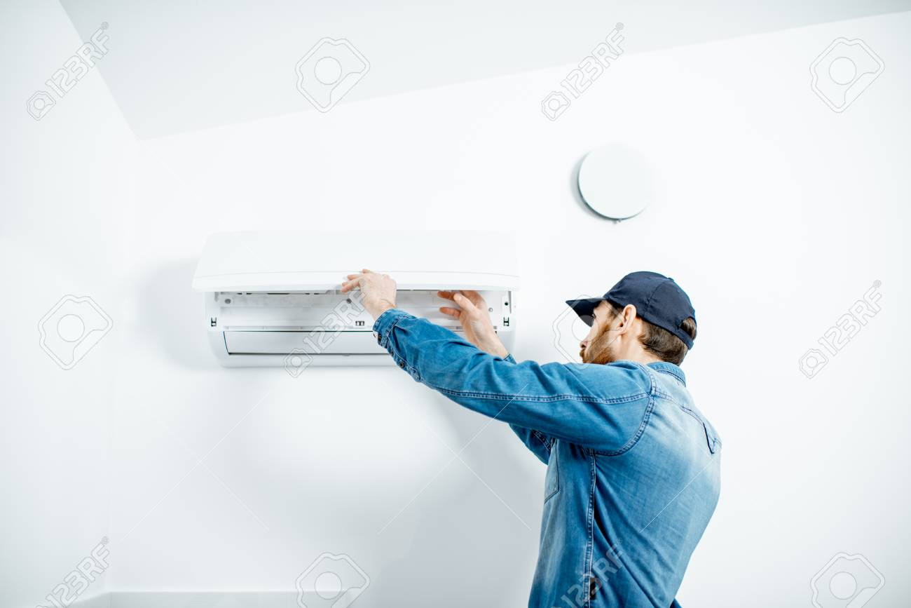 Repairman in blue workwear serving the air conditioner changing filter on the white wall background - 118140083