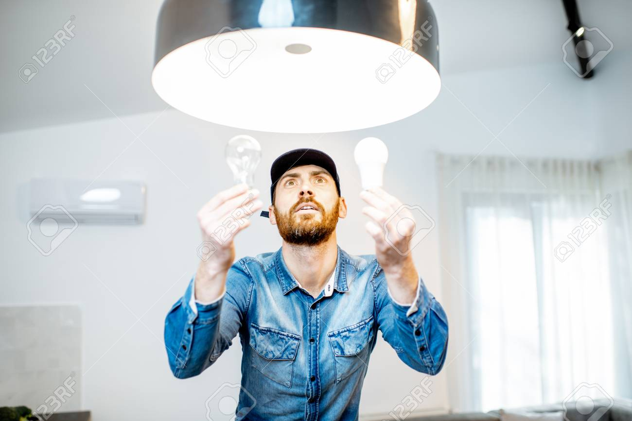 Handyman choosing between energy save and cheap incandescent lamp while changing light in the appartment - 118140142