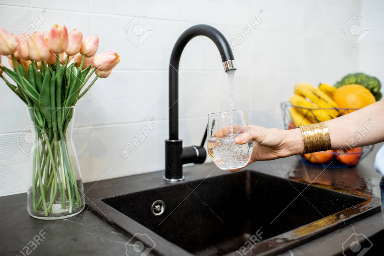 Woman filling glass with tap water for drinking on the kitchen - 118140423