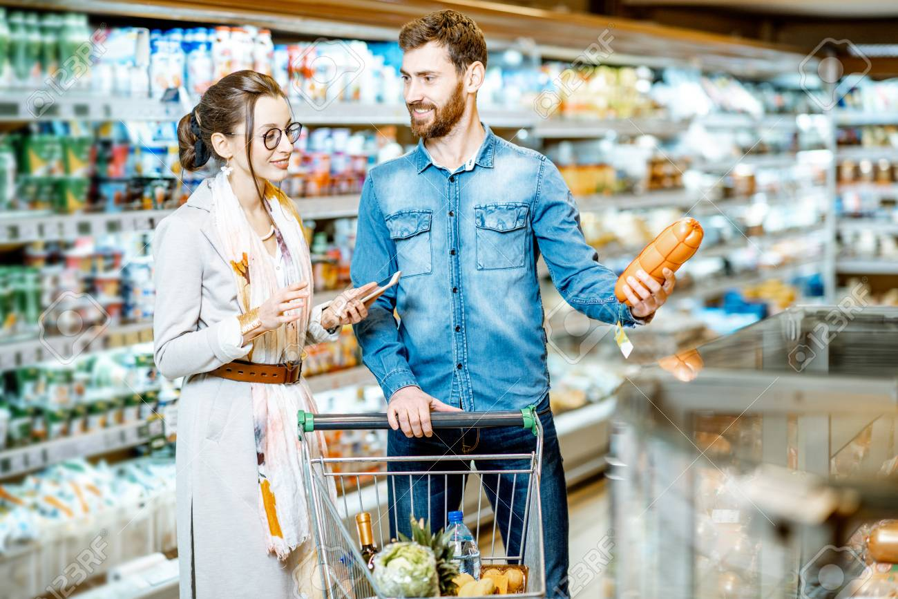 Young Couple Buying Food Standing With Shopping Cart In The Supermarket