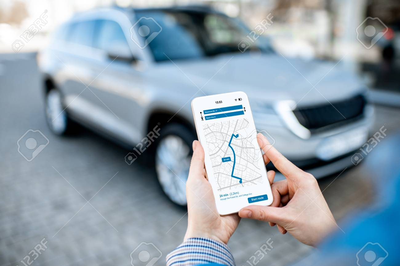 Woman using smart phone with navigation app, close-up view with modern car on the background - 119987400