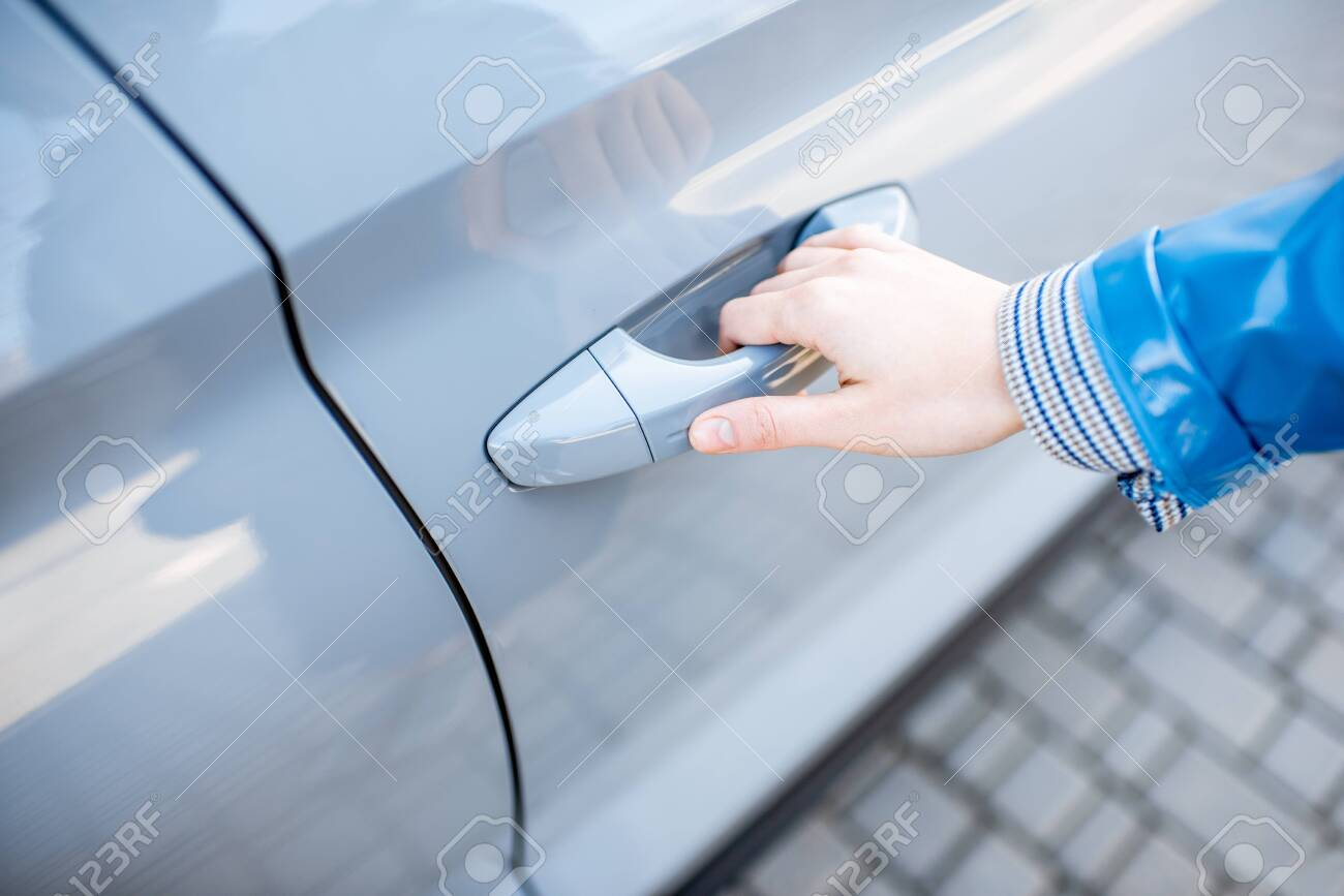 Woman pulling door handle of the modern car, close-up view. Concept of the keyless access to the car - 119987404