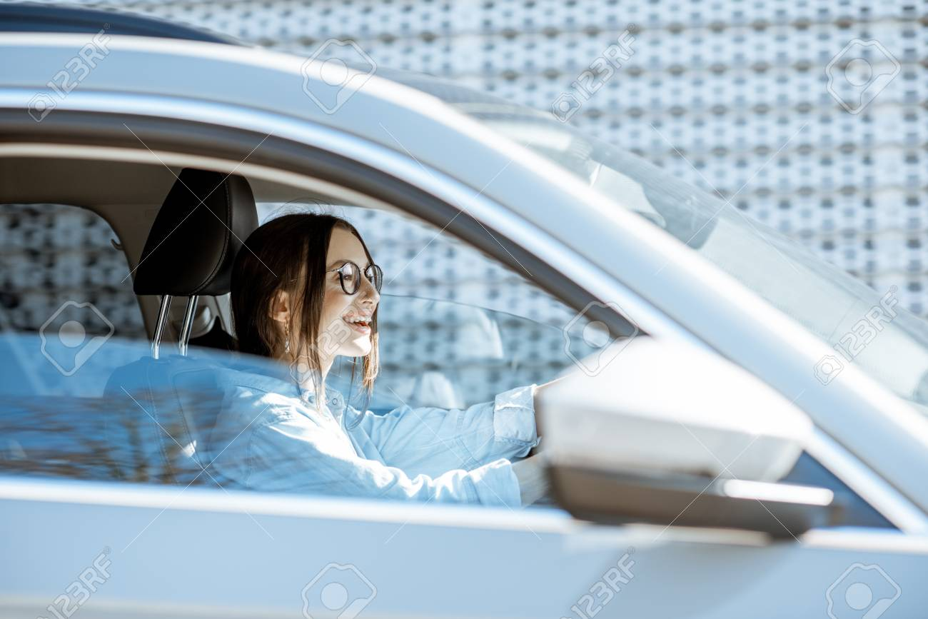 Young and happy woman driving luxury car in the city, side view through the door window - 119987463