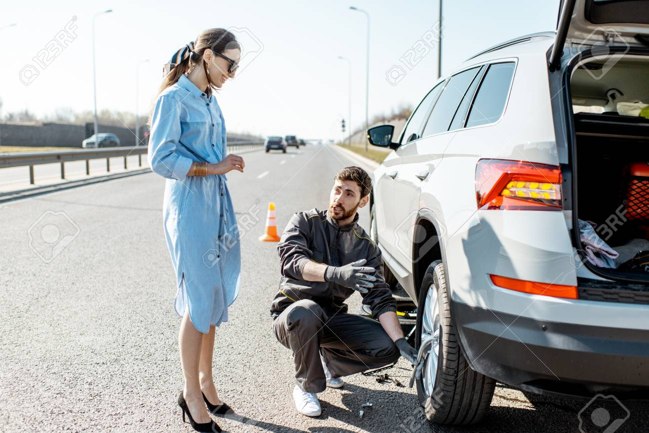 Road assistance worker helping young woman to change a car wheel on the highway - 120349181