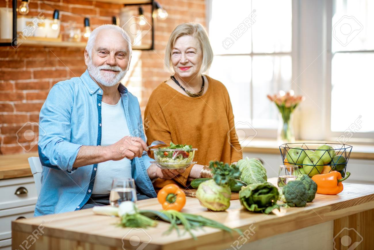 Cheerful senior couple eating salad standing together with healthy food on the kitchen at home. Concept of healthy nutrition in older age - 120618464