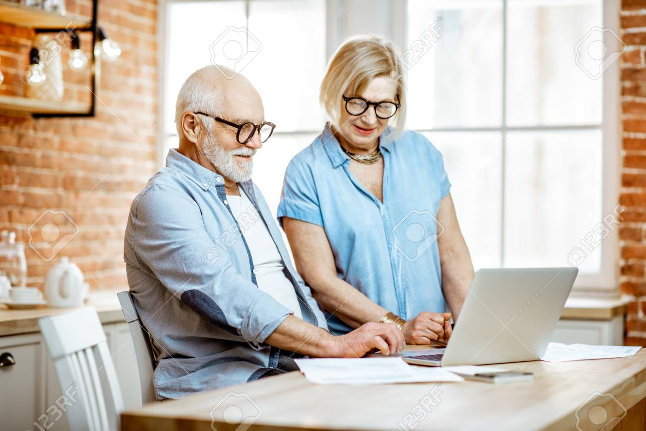 Beautiful senior couple in blue shirts working together with laptop on the kitchen at home - 121137846