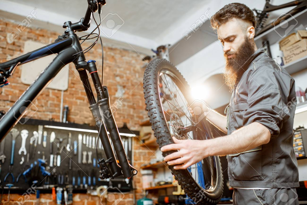 Handsome repairman in workwear serving mountain bicycle, standing with front wheel at the workshop of a bicycle shop - 121320549