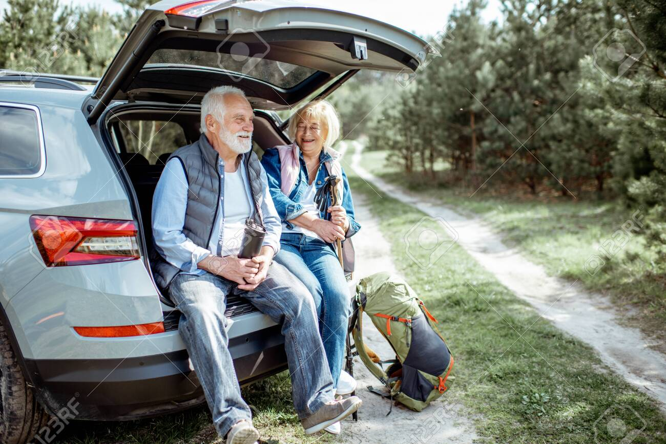 Senior couple sitting at the car trunk, enjoying nature while traveling in the young pine forest - 122705783