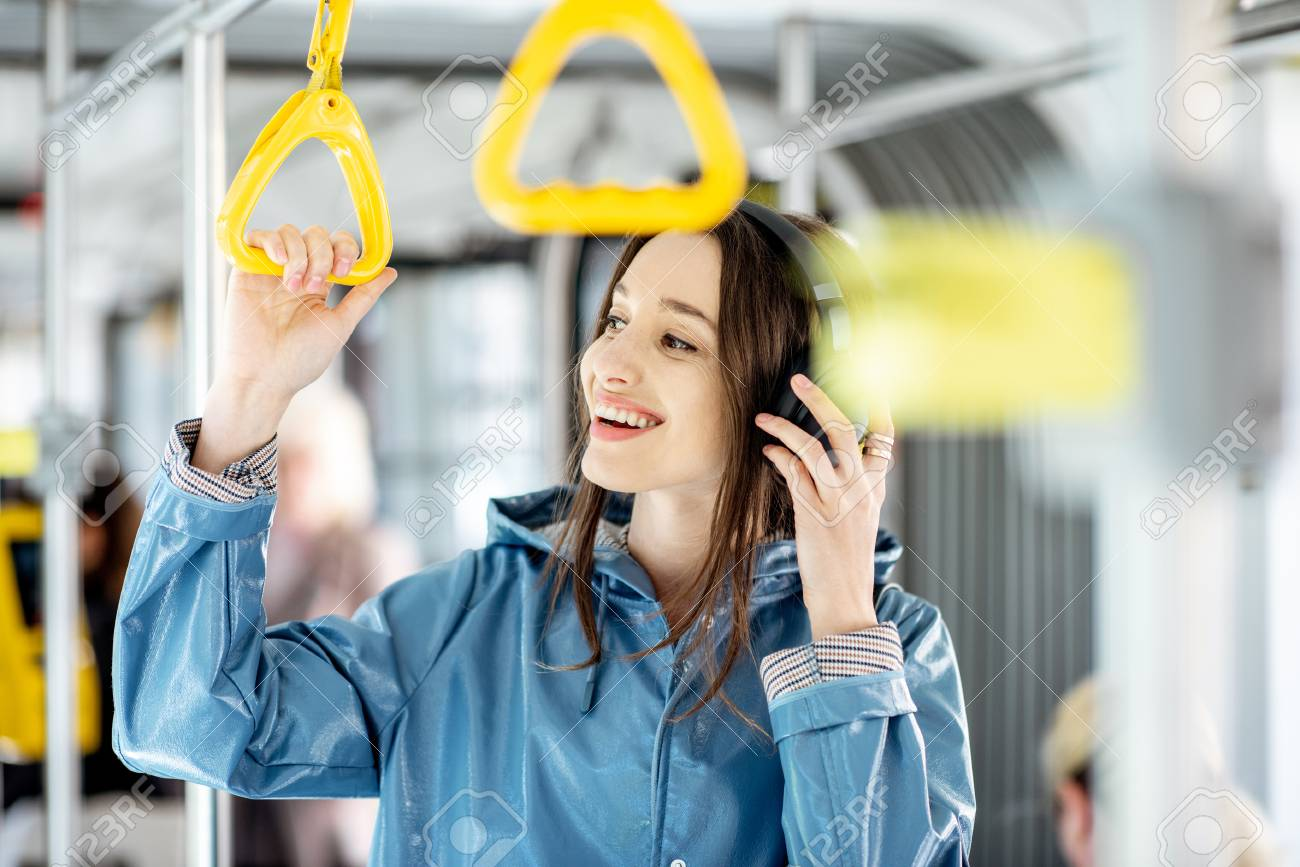 Young stylish woman enjoying trip in the public transport, standing with headphone while moving in the modern tram - 122705628