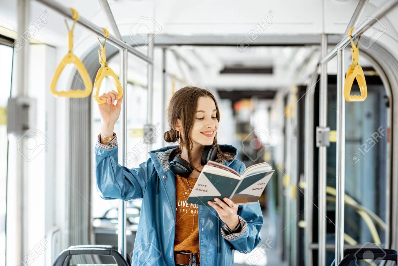 Young woman reading book while standing in the modern tram, happy passenger moving by comfortable public transport - 123396471