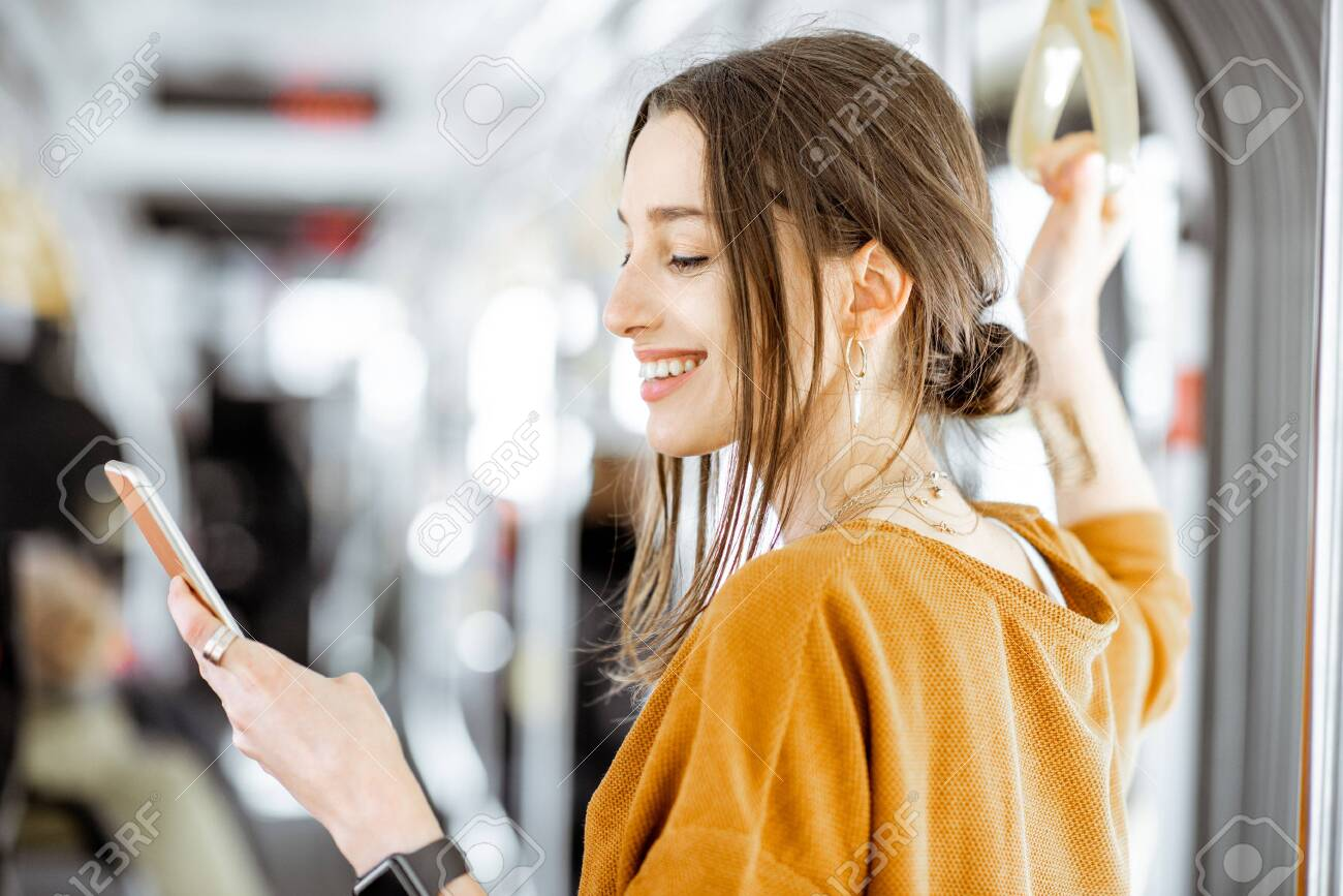 Close-up portrait of a young woman using smartphone while standing in the modern tram - 123396880