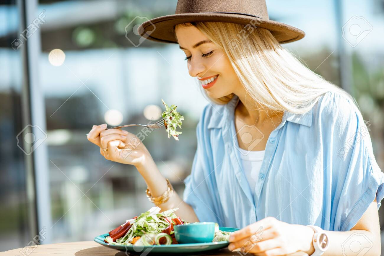 Stylish young woman eating healthy salad on a restaurant terrace, feeling happy on a summer day - 129889204