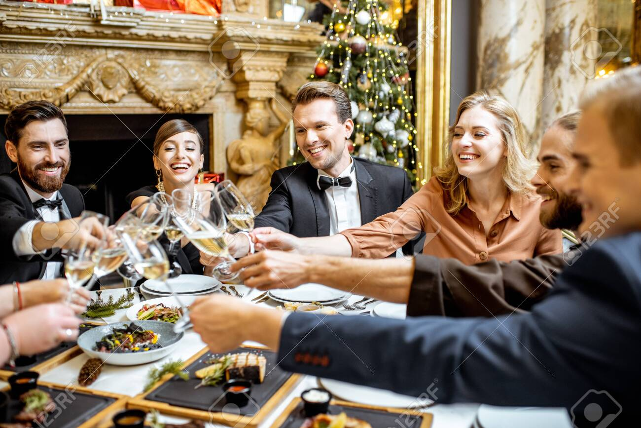 Elegantly dressed group of people having fun, clinking wine glasses during a festive dinner near the fireplace and christmas tree, celebrating New Year holiday at the luxury restaurant - 132844877