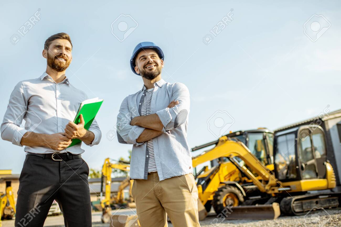 Builder choosing heavy machinery for construction with a sales consultant standing with some documents on the open ground of a shop with special vehicles - 133043762