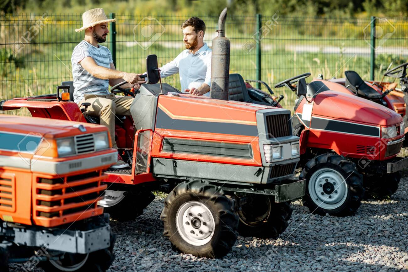Young agronomist with elegant salesman choosing a tractor for farming on the open ground of agricultural shop - 133043015