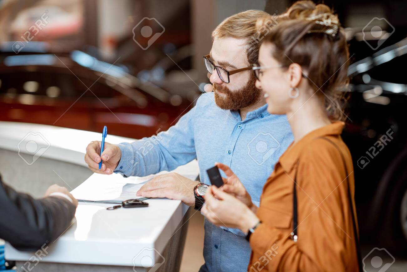 Young couple signing some documents, buying a new car in the modern showroom of the car dealership - 134733337