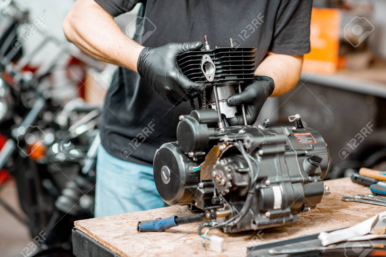 Workman disassembling motorcycle engine during a repairment at the working table of the workshop, close-up with no face - 133183254