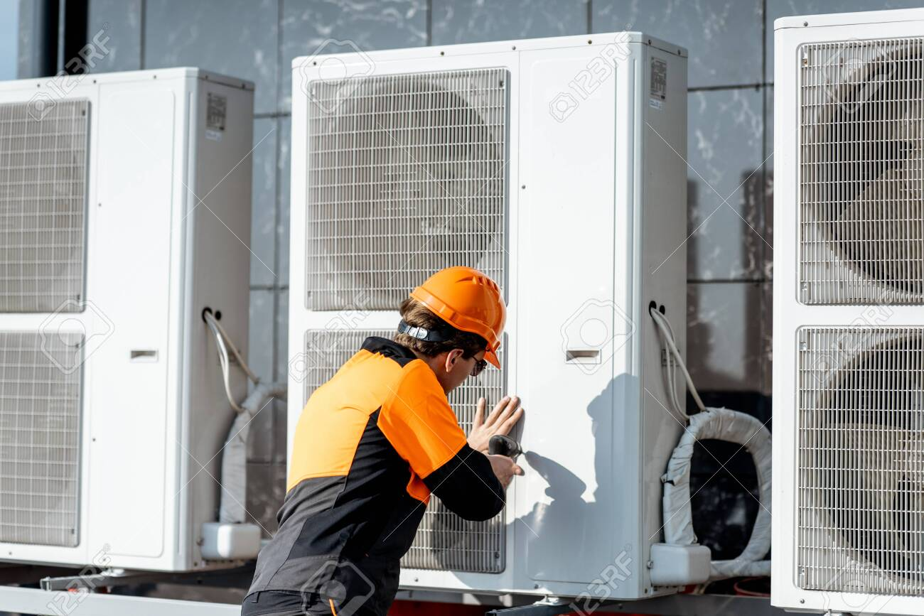 Professional workman in protective clothing installing or reparing outdoor unit of the air conditioner or heat pump on the rooftop - 133698251