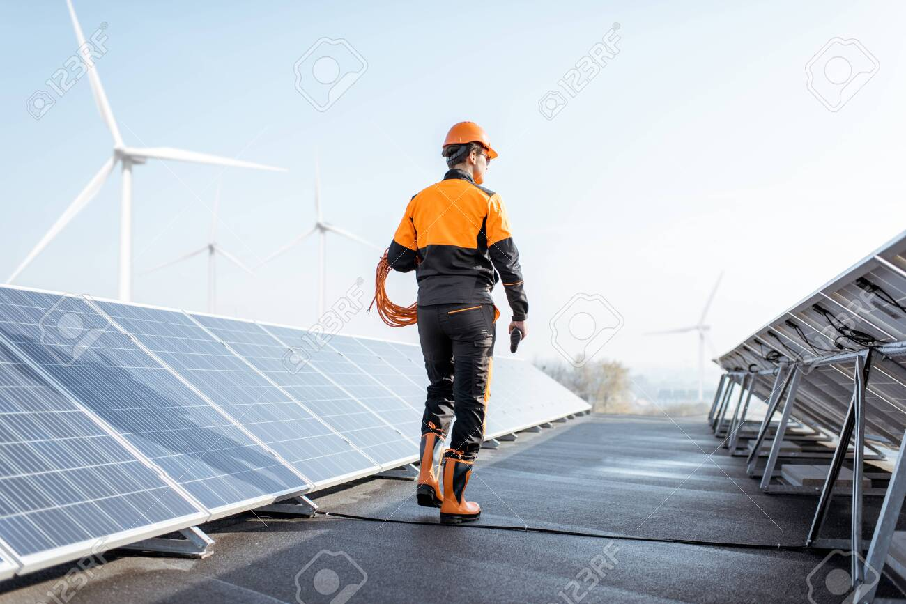 Well-equipped worker in protective orange clothing walking and examining solar panels on a photovoltaic rooftop plant. Concept of maintenance and installation of solar stations - 133475020