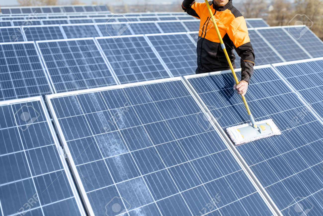Professional cleaner in protective workwear cleaning solar panels with a mob. Concept of solar power plant cleaning service - 133503673