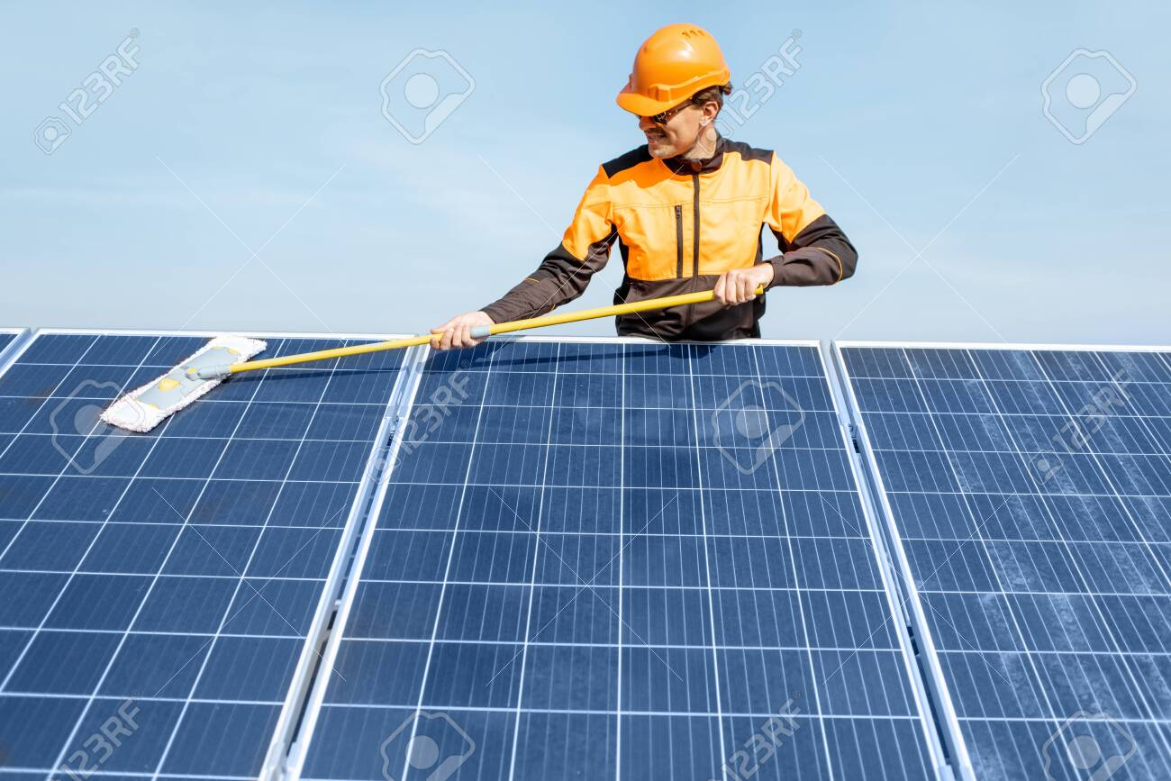 Professional cleaner in protective workwear cleaning solar panels with a mob. Concept of solar power plant cleaning service - 133698292