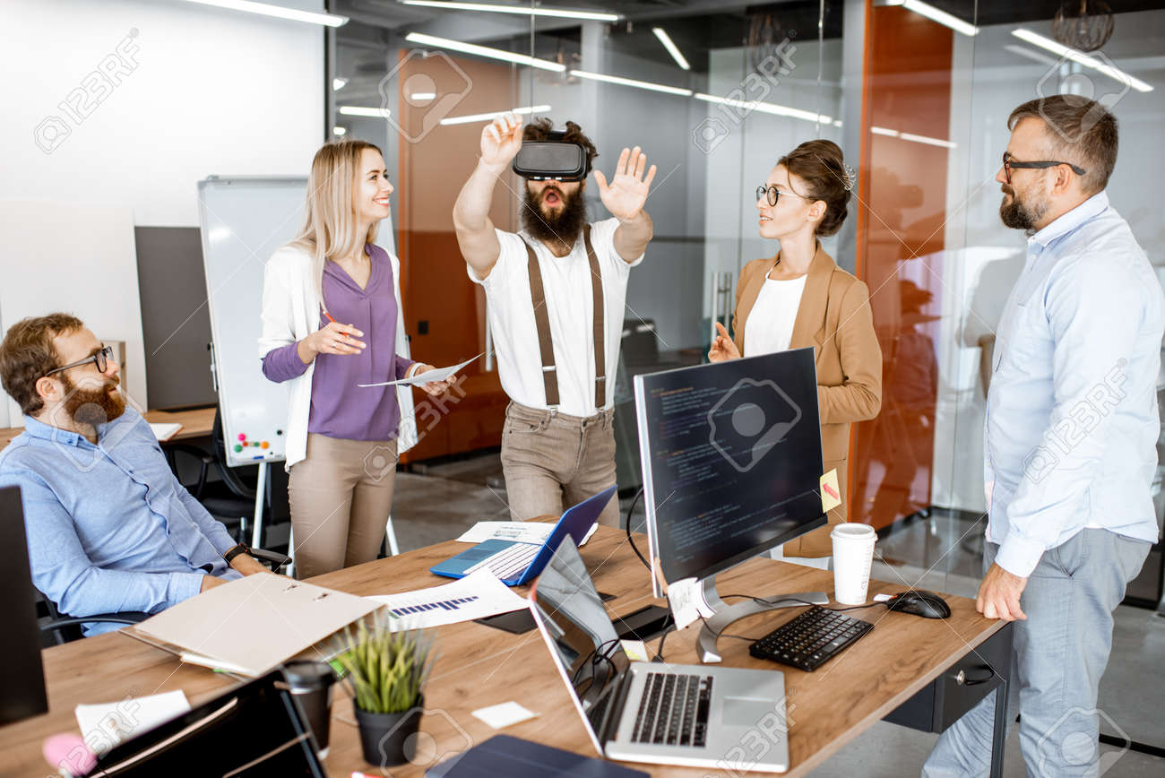 Group of diverse colleagues during small conference in the office, creative bearded man trying a new product with virtual reality goggles - 133503964