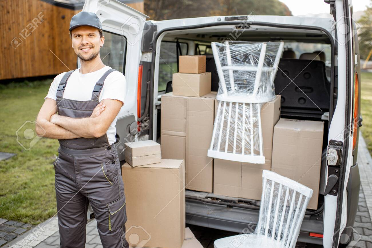 Portrait of a handsome delivery man in uniform standing near a cargo van vehicle trunk full of boxes and furniture during a relocation - 133917860