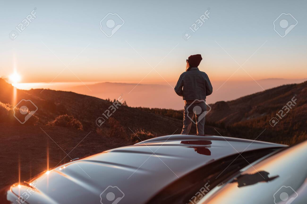 Landscape view on the roadside above the clouds with woman enjoying beautiful sunset while traveling on the convertible sports car - 139036670