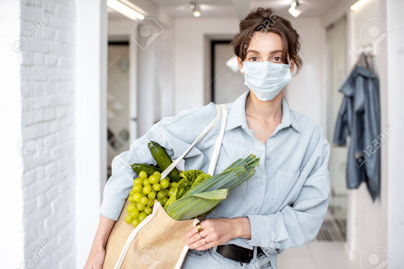 Young woman in medical mask coming home with shopping bag full of fresh food. Concept of lifestyle during an epidemic or bad air pollution - 143061771
