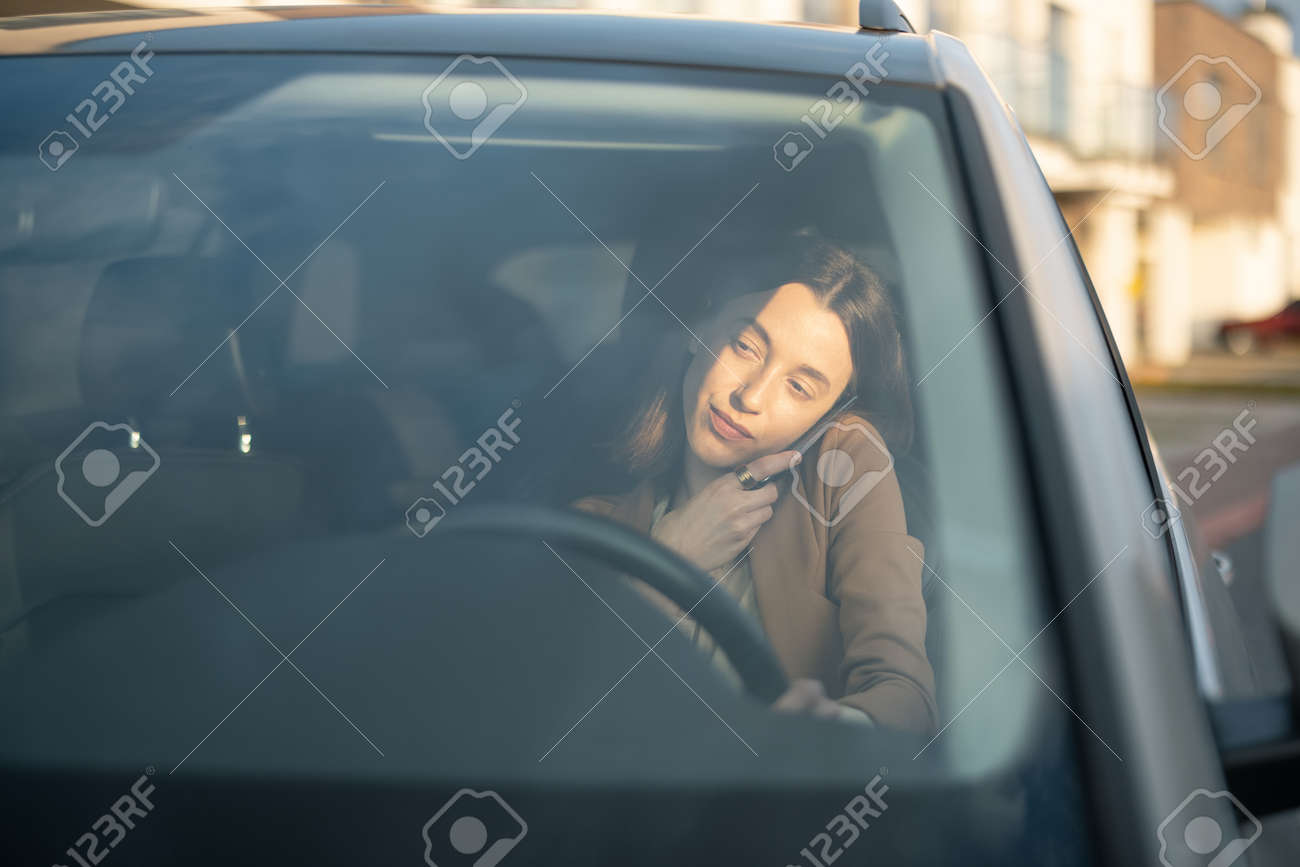 Young woman talking on the phone and driving a car - 167030284