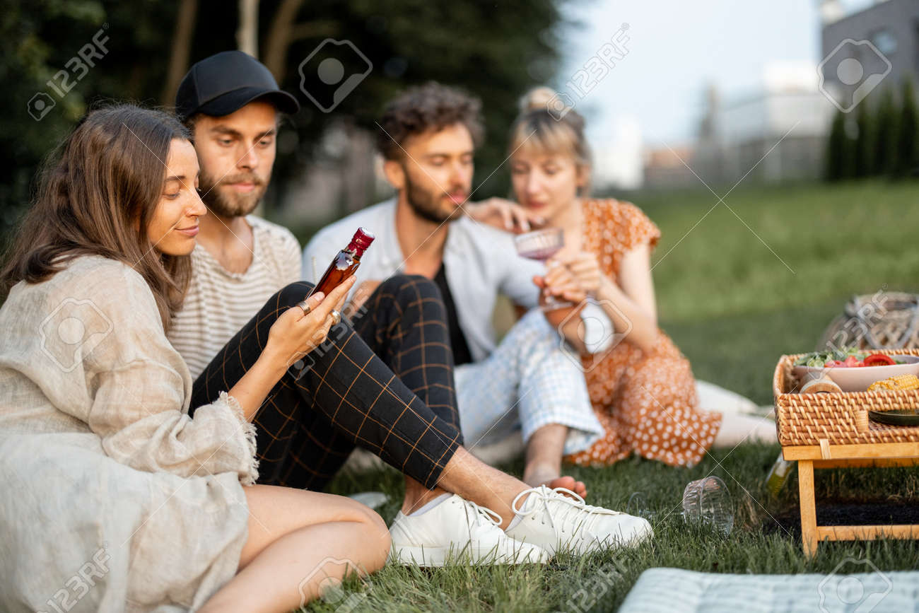 Young friends sit together and hug, talk and drink alcohol in a close and friendly atmosphere on a picnic in the evening - 172037521