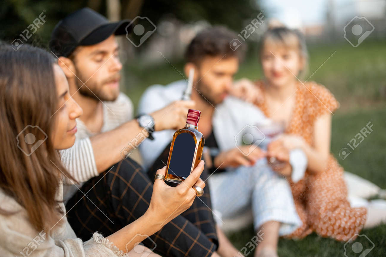 Young friends sit together and hug, talk and drink alcohol in a close and friendly atmosphere on a picnic in the evening. Woman holding bottle with blank label to copy paste - 172037487
