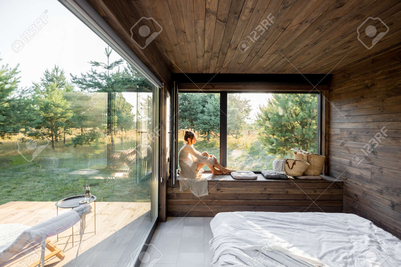 Young woman resting at beautiful country house or hotel, sitting on the window sill enjoying beautiful view on pine forest. Concept of solitude and recreation on nature - 172224119