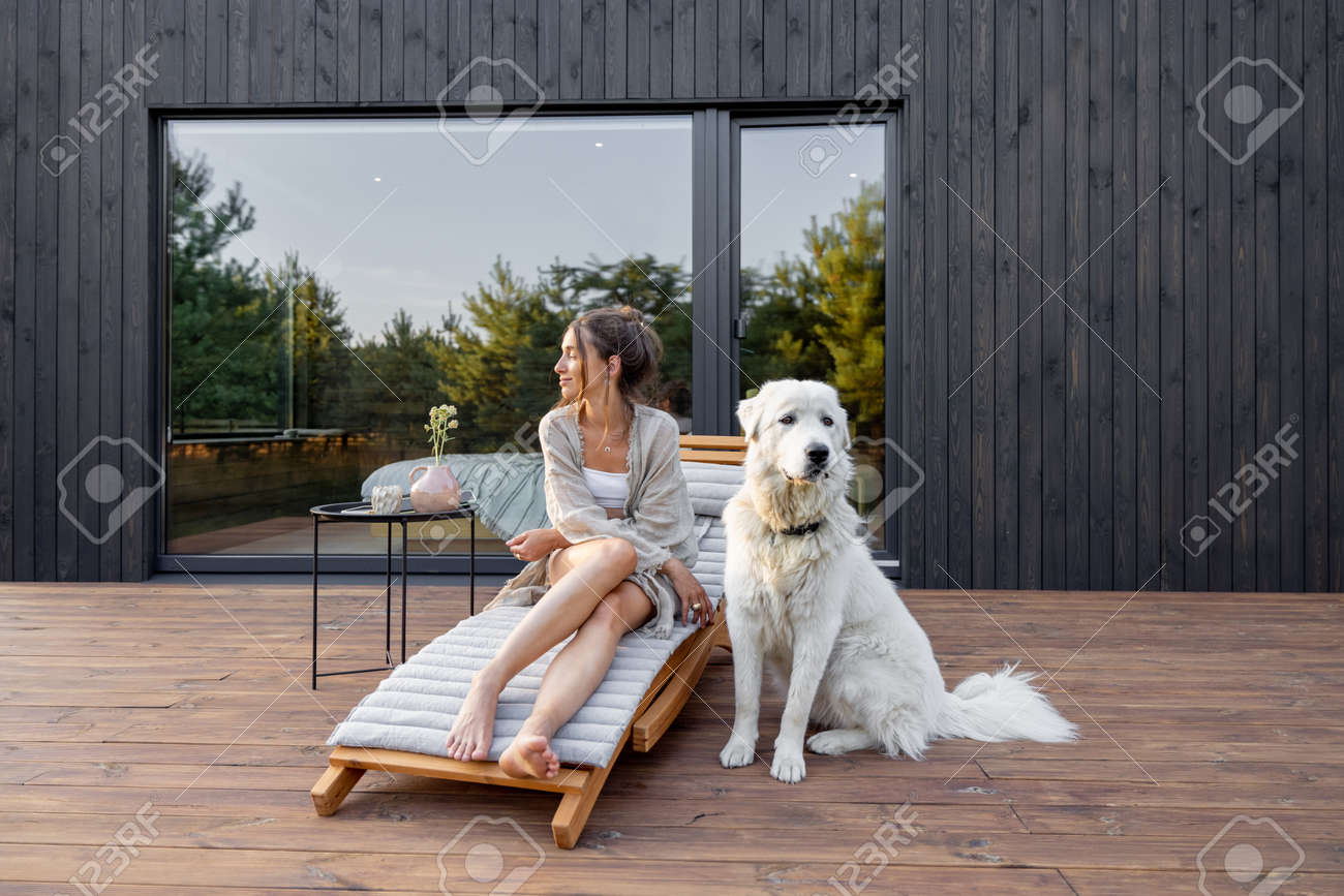 Woman enjoys the nature while sits on sunbed on wooden terrace near the modern house with panoramic windows near pine forest whith big white dog. Concept of solitude and recreation on nature - 172224238