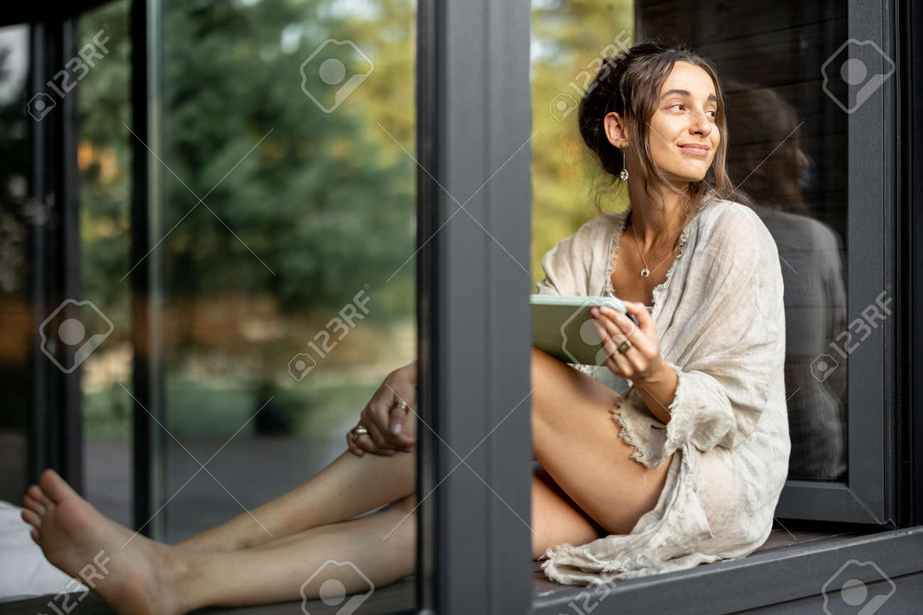 Young cheerful woman enjoy of resting at modern house or hotel, sitting with tablet on the window sill and looking at pine forest. View from outside. Beautiful destinations for vacation - 172224302