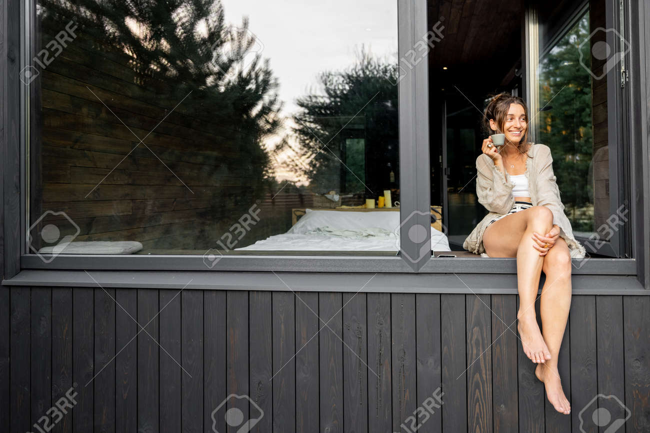 Young woman resting at modern house or hotel in pine forest, sitting on the window dangling her legs outside and enjoying calmness and quietness. Beautiful destinations for vacation. Copy space - 172224323