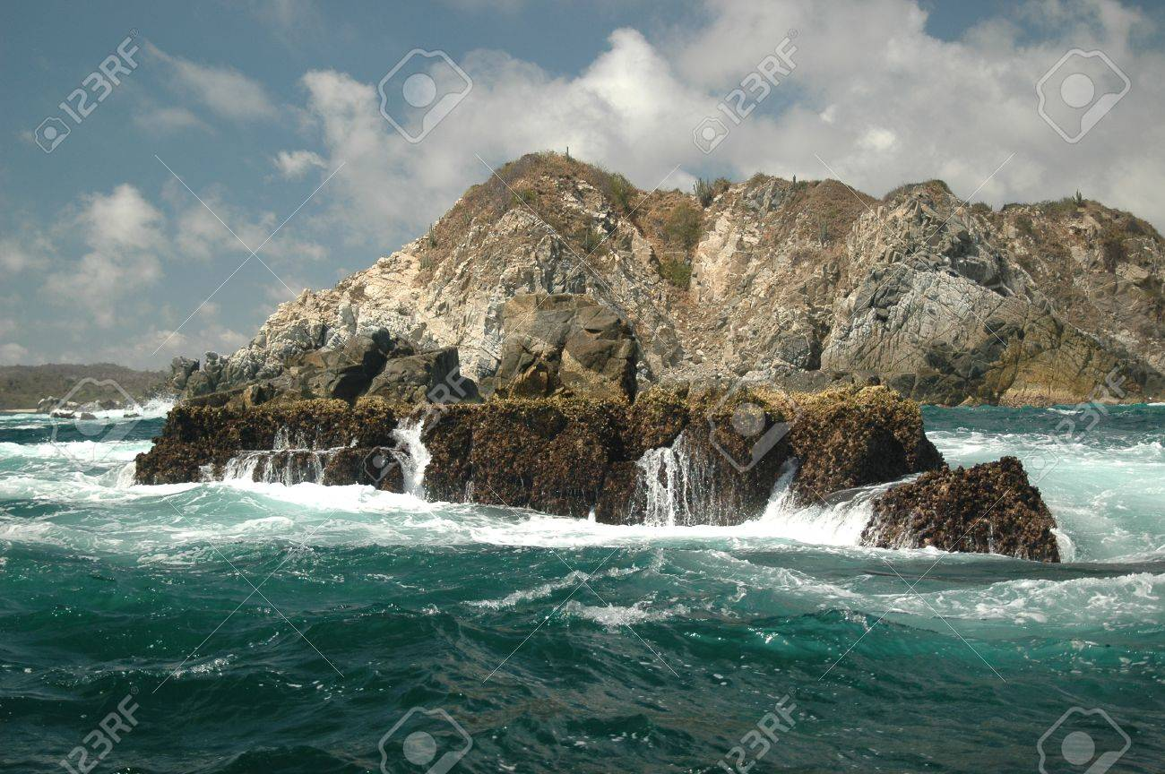 Rough surf near Huatulco, Mexico. Waves pounding on the rocky shore and islands near the coastline. Stock Photo - 10175938
