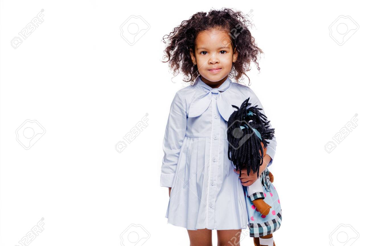 Portrait of a cute little african american girl hugging doll, isolated on white background - 153345788