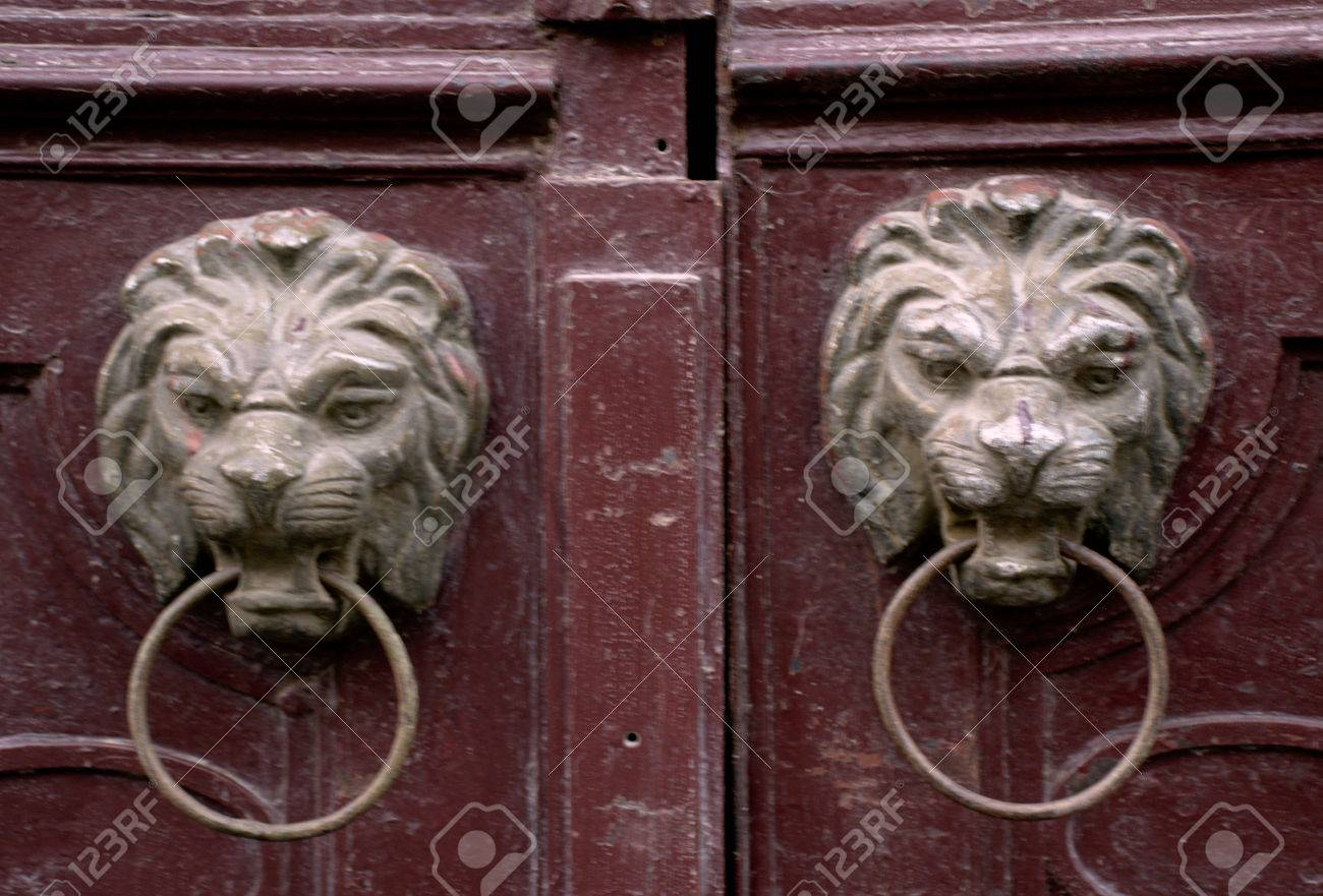 bronce golpeadores len simtricas en las puertas antiguas de madera de color rojo foto de archivo