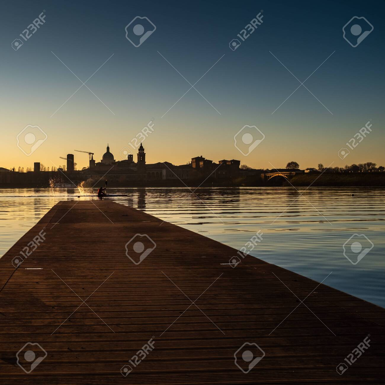 Adult male kayaker splashing water with paddle while kayaking on the Lago Inferiore (Inferior Lake) in front of the suggestive medieval profile of the Old Town of Mantua (Lombardy,Italy). - 138447488
