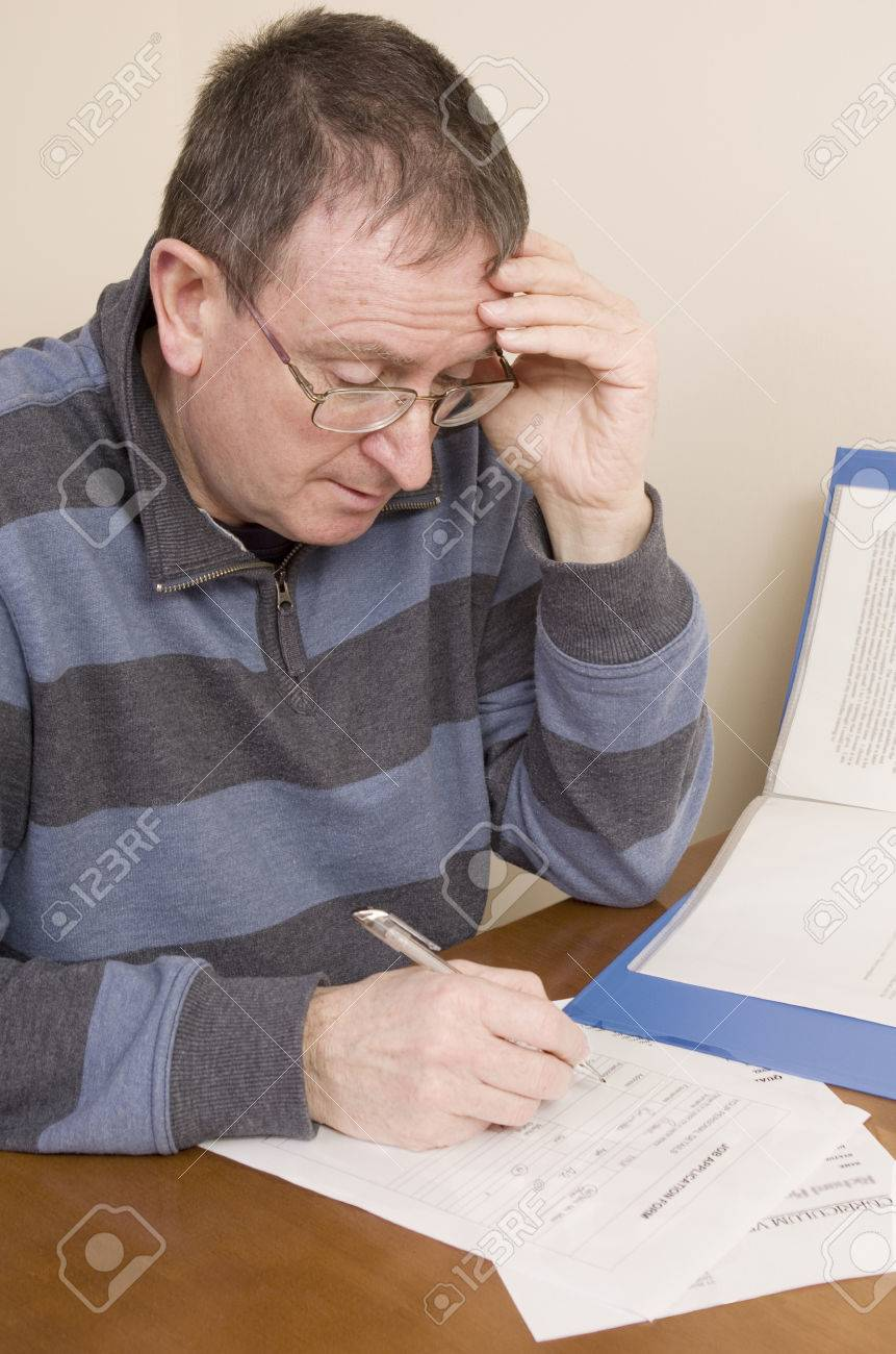 unemployed man searching for a job and completing a job stock photo unemployed man searching for a job and completing a job application form