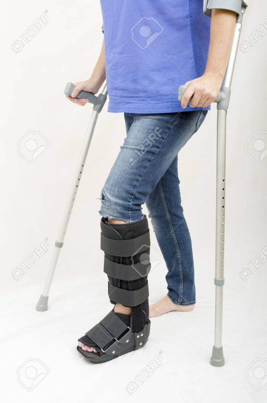 A Lady With A Fractured Leg In An Orthopaedic Boot Walking With ...