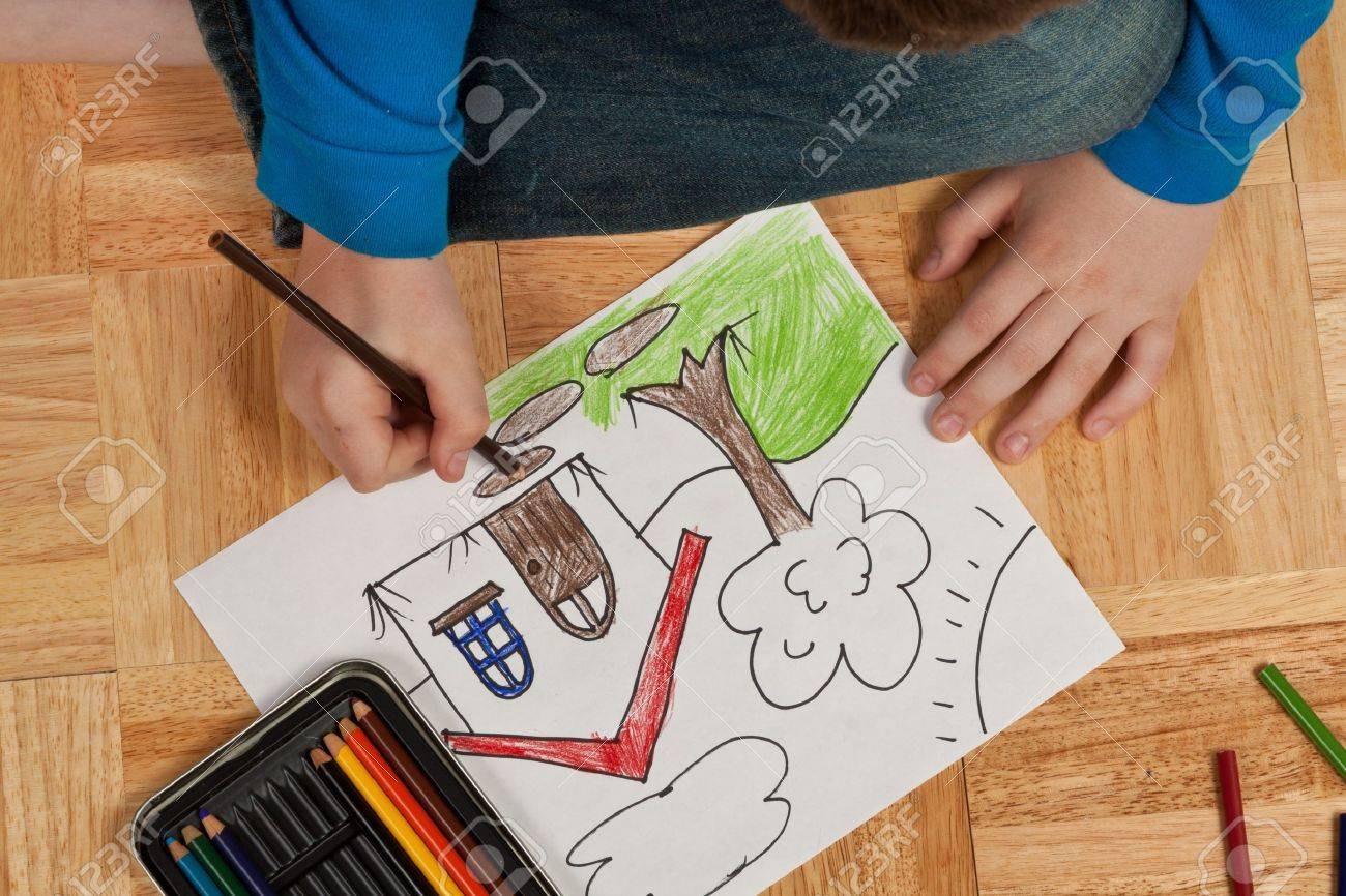 Young Boy In Blue Shirt Coloring A Picture With Pencils While ...