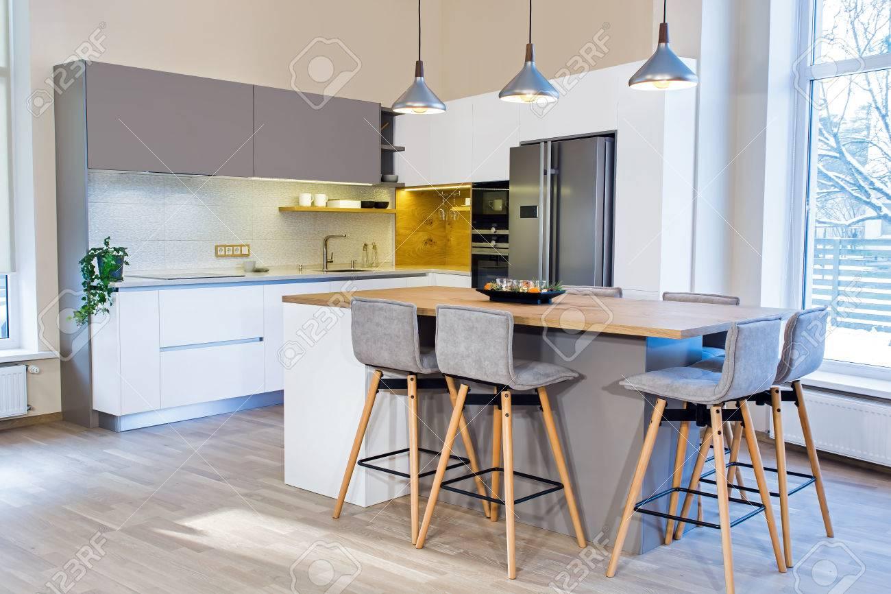 Interni moderni. Design moderno della cucina in interni luminosi. C\'è anche  un\'isola della cucina nella stanza. Cucina e soggiorno combinati. ...