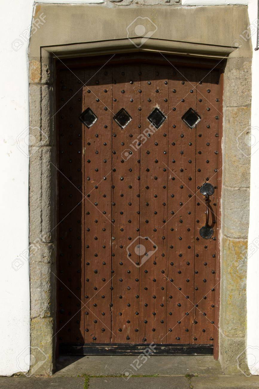 A reinforced antique oak door with rivets, handle and small windows set in  a stone - A Reinforced Antique Oak Door With Rivets, Handle And Small Windows