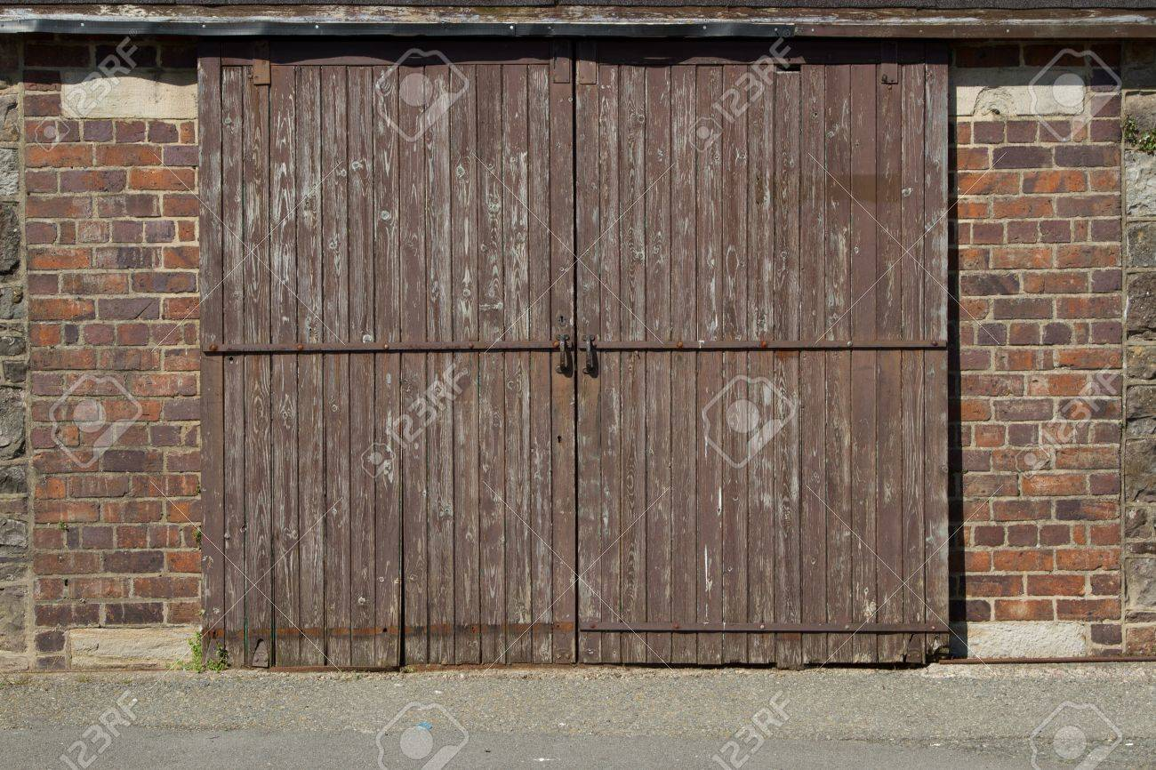 A Wooden Garage Door With Lock And Handles And Red Brick Walls