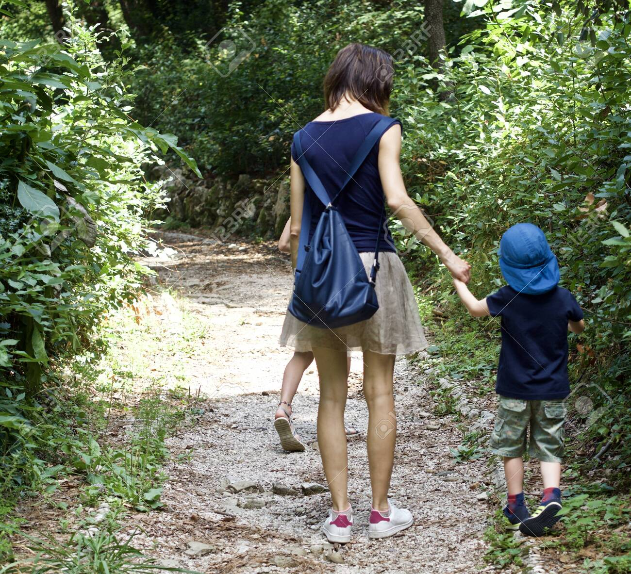 a happy mother is walking with her kids through a forest - 134791315
