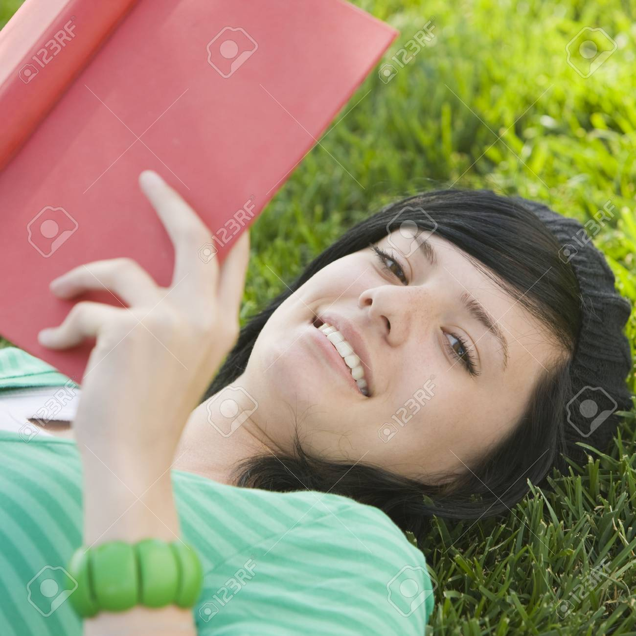Happy teen studies with book in the grass Stock Photo - 3569516