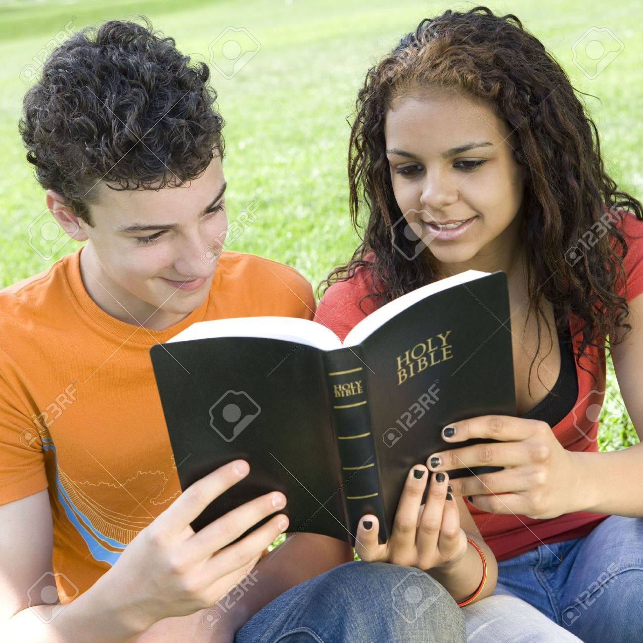 Two teens share a bible in a park Stock Photo - 3569719