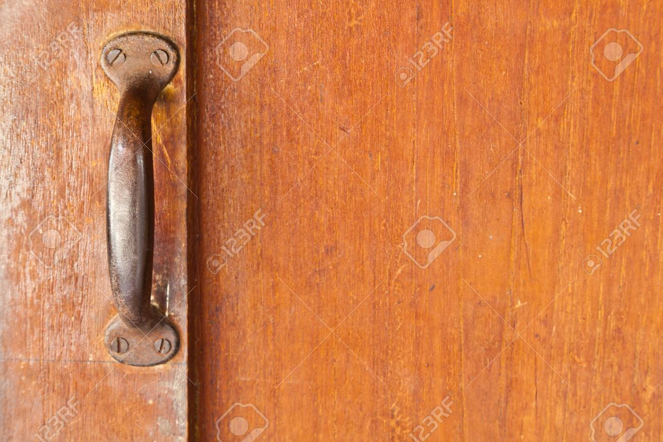 The old metallic handle attached on the wooden door - 16801967